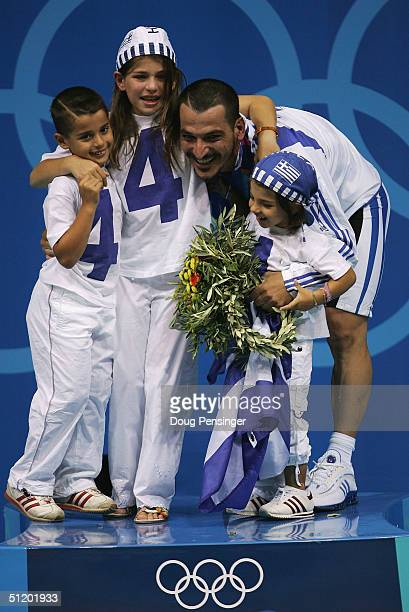 Pyrros Dimas of Greece celebrates with his children Helen, Victor and Maria after winning the bronze medal for the men's 85 kg category weightlifting...