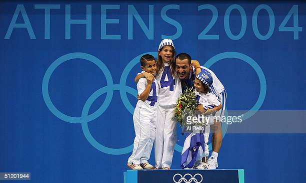 Pyrros Dimas of Greece celebrates with his children Helen, Victor and Maria after winning the bronze medal in the men's 85 kg category weightlifting...