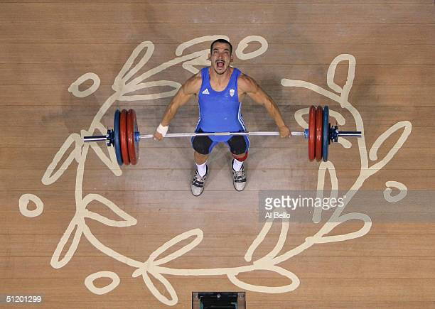 Pyrros Dimas of Greece shouts as he attempts to make a lift in the men's 85 kg category weightlifting competition on August 21 2004 during the Athens...