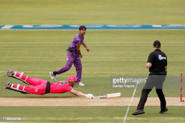 Qais Ahmand of the Hurricanes attempts to run out Jordan Silk of the Sixers during the Big Bash League match between the Hobart Hurricanes and the...