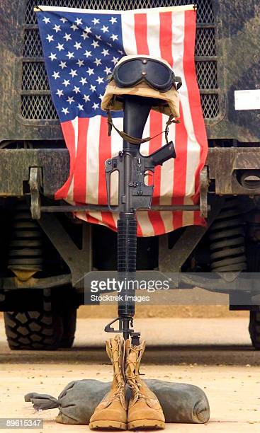 qalat sikar air base, iraq, april 27, 2003 - an m16-a2 service rifle, a pair of boots and a helmet stand in tribute to a fallen marine corps sergeant, killed in action in iraq during operation iraqi freedom.   - boots rifle helmet stock pictures, royalty-free photos & images