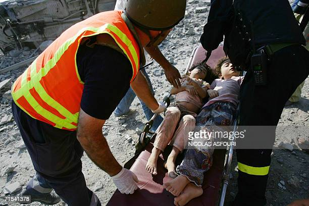 Lebanese Red Cross rescue workers push the the bodies of two girls on a stretcher through the rubble after Israeli air strikes on the southern...