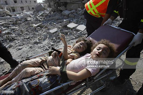 Red Cross rescue workers push the the bodies of two girls on a stretcher through the rubble after Israeli air strikes on the southern village of Qana...