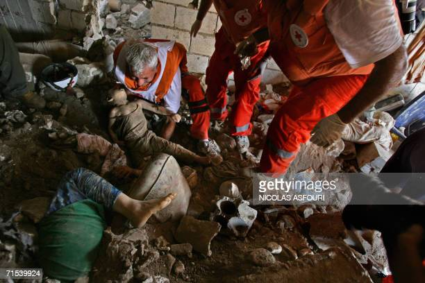 Red Cross rescuers extract the body of a girl from the rubble of a destroyed house after Israeli air strikes on the southern Lebanese village of Qana...