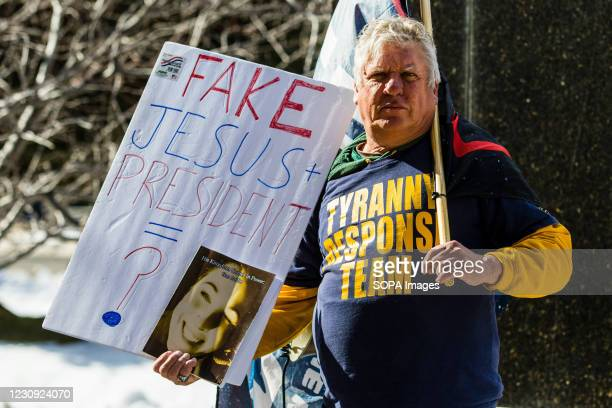 Qanon believer holds a placard during the demonstration. Protesters gathered at the state's legislative building to protest various causes such as...
