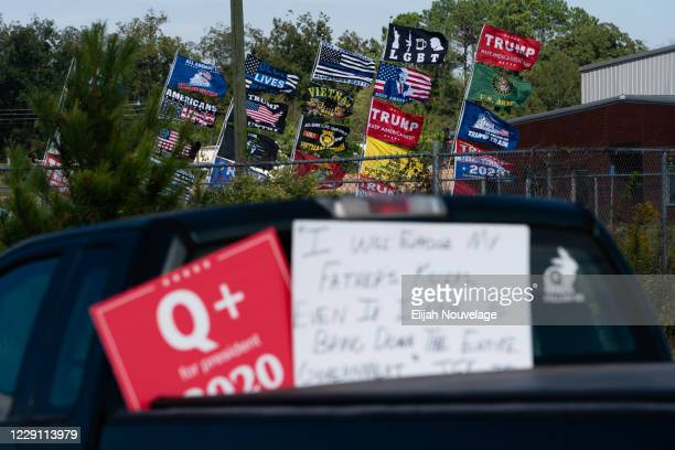 """QAnon"""" sign is seen on a truck in the parking lot for President Trump's rally on October 16, 2020 in Macon, Georgia. President Donald Trump continues..."""