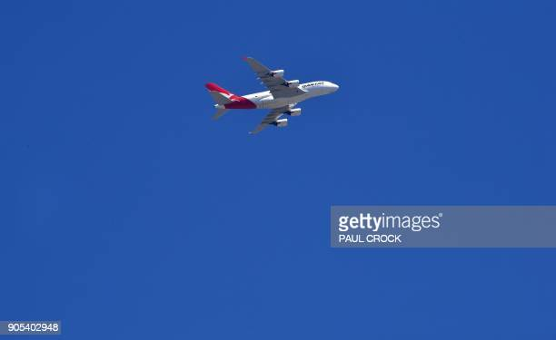 A Qantas A380 airplane flies over Melbourne on January 16 2018 / AFP PHOTO / Paul Crock