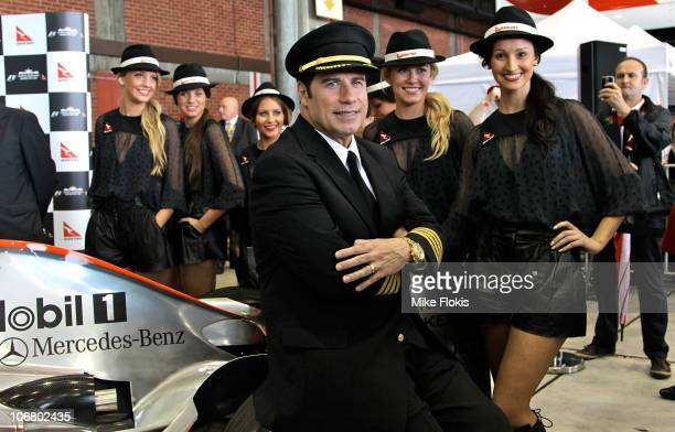 Qantas Ambassador John Travolta poses for a photo on a Formula 1 car at Qantas' 90th birthday celebrations at Melbourne Tullamarine Airport on...