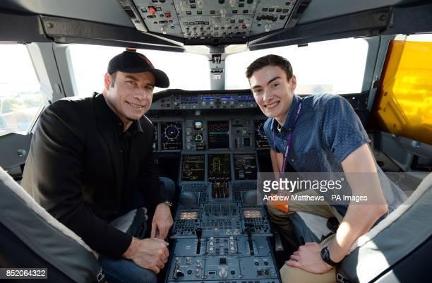 Qantas ambassador John Travolta sits in the cockpit of a Qantas Airbus A380 with Tom Hall 18 from Perth Scotland at Heathrow Airport London
