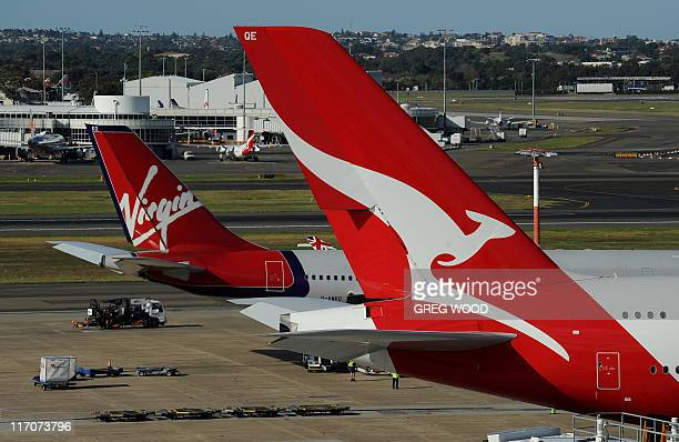 A Qantas and a Virgin plane sit on the tarmac at the international airport in Sydney on June 21 2011 Thousands of passengers were grounded on June 21...