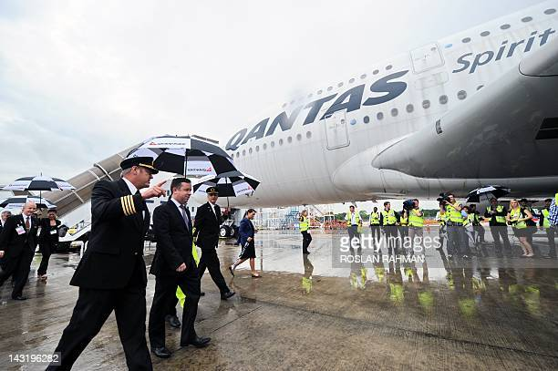 Qantas chief executive Alan Joyce walks with Qantas pilot captain Richard de Crespigny and captain David Evans in front of Qantas Airbus A380 jet...
