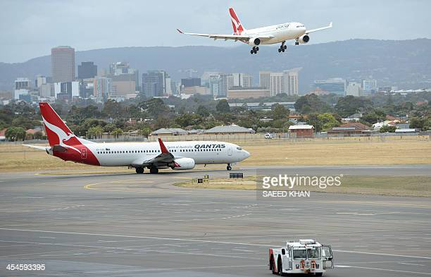 A Qantas flight is on final approach as another Qantas aircraft taxis at Adelaide airport on December 10 2013 Embattled Australian carrier Qantas'...