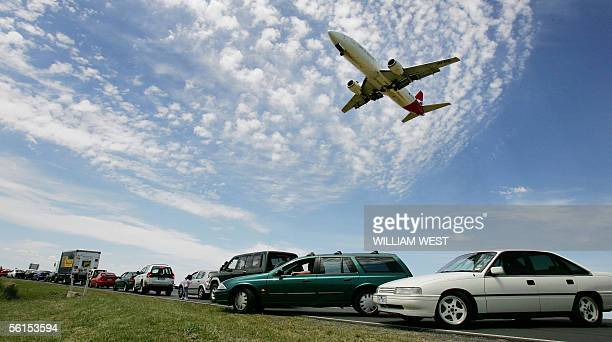 Qantas jet passes over the road as thousands of people create a major traffic jam as they watch the new Airbus A380 land at Melbourne's Tullamarine...