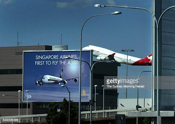 A Qantas plane takes off from Sydney Airport while a Singapore Airlines billboard can be seen in front 21 March 2006 SMH Picture by PETER MORRIS