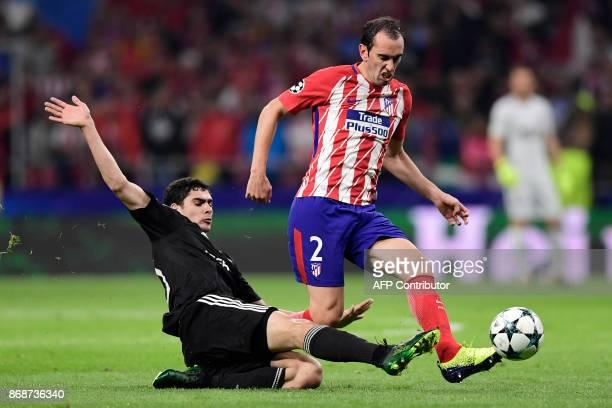 Qarabag's Azerbaijani forward Ramil Sheydaev tackles Atletico Madrid's Uruguayan defender Diego Godin during the UEFA Champions League football match...