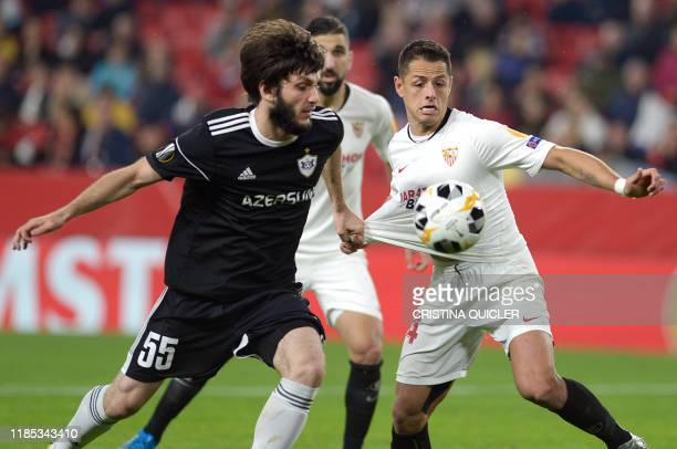 Qarabag's defender Badavi Huseynov fights for the ball with Sevilla's Mexican forward Chicharito during the UEFA Europa League Group A football match...