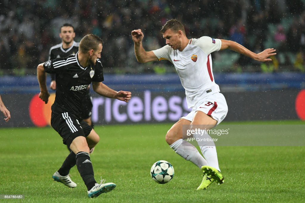 Qarabag's defender from Azerbaijan Maksim Medvedev (L) and Roma's forward from Bosnia-Herzegovina Edin Dzeko vie for the ball during the UEFA Champions League Group C football match between Qarabag FK and AS Roma in Baku on September 27, 2017. / AFP PHOTO / Vano Shlamov
