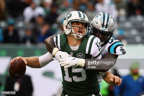 Qarterback Josh McCown of the New York Jets is sacked by defensive end Mario Addison of the Carolina Panthers during the third quarter of the game at...