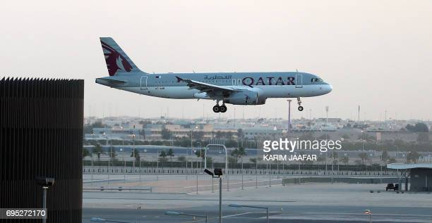 Qatar Airways Airbus A320 aircraft lands at the Hamad International Airport in the Qatari capital Doha on June 12, 2017. - Qatar Airways called on...