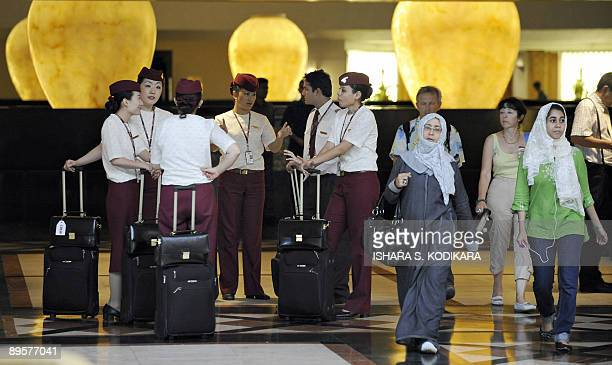 Qatar Airways cabin crew wait to check into a fivestar hotel as other guests walk past in Sri Lanka's capital of Colombo on August 3 2009 Sri Lanka...