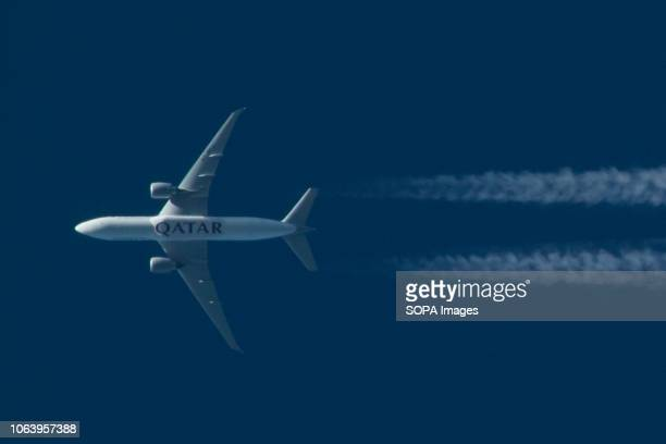 Qatar Airways Cargo Boeing 777F seen flying over Thessaloniki, Greece. The airplane is flying from Doha, Qatar to Luxembourg. The airplane has the...