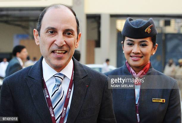 Qatar Airways CEO Akbar Al Baker and a crew membe proceed to a Boeing 777 for a photo call after the company's press conference at the India Aviation...
