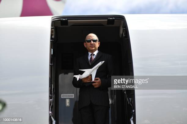 Qatar Airways CEO Akbar Al Baker holds a model of a Gulfstream G500 Executive Jet as he enters his Gulfstream G500 Executive Jet during its launch at...