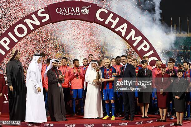 Qatar airways CEO Akbar Al Baker presents the trophy to Andres Iniesta of Barcelona after winning the friendly soccer match between AlAhli Saudi and...