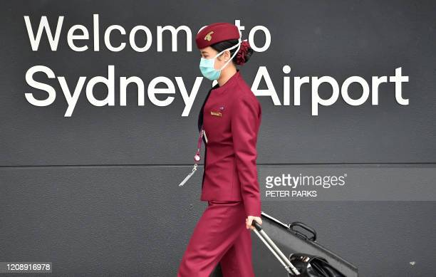 Qatar Airways crew member enters Sydney international airport to fly on a repatriation flight back to France on April 2, amid the COVID-19...