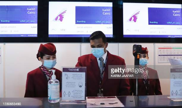 Qatar Airways employees wait at the boarding counter ahead of the first flight bound for Cairo after the resumption of flights between Qatar and...