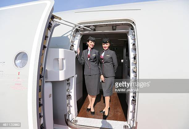 Qatar Airways flight stewardess pose for a photo on a new Airbus A350XWB at the Doha international airport in Doha on January 72015 Qatar Airways...