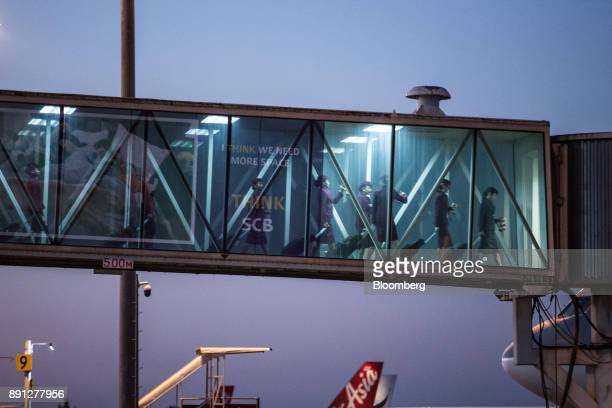Qatar Airways Ltd aircrew walk along a passenger boarding bridge while disembarking from a flight to Chiang Mai International Airport in Chiang Mai...