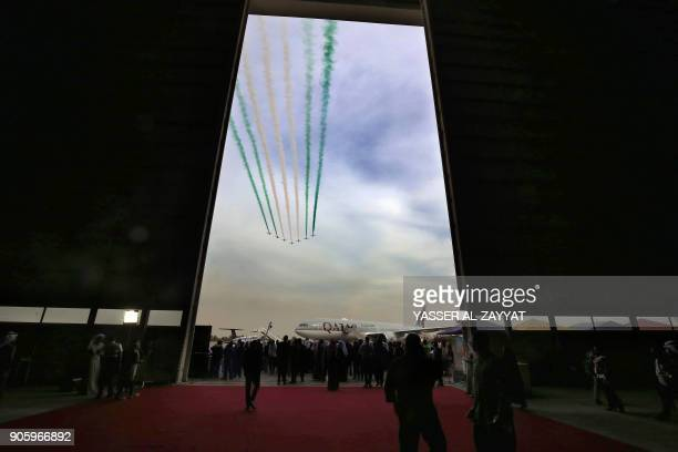A Qatar Airways plane in seen on the tarmac as Saudi falcon Hawk Mk 65 aircrafts perform during the Kuwait aviation show in Kuwait City on January 17...