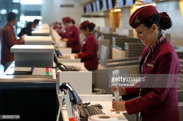 A Qatar Airways stewardess waits for customers at the checkin counter at the Hamad International Airport in Doha on July 20 2017 / AFP PHOTO /...