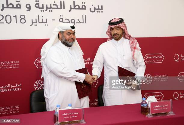 Qatar Charity CEO Yousef bin Ahmed Al Kuwari and Qatar Pharma Chairperson Dr Ahmed bin Mohammed Al Sulaiti shake hands after signing the agreement to...