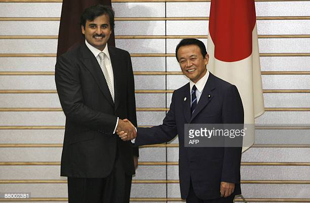 Qatar Crown Prince Sheikh Tamim Bin Hamad Al Thani shakes hands with Japanese Prime Minister Taro Aso before a meeting at Aso's official residence in...