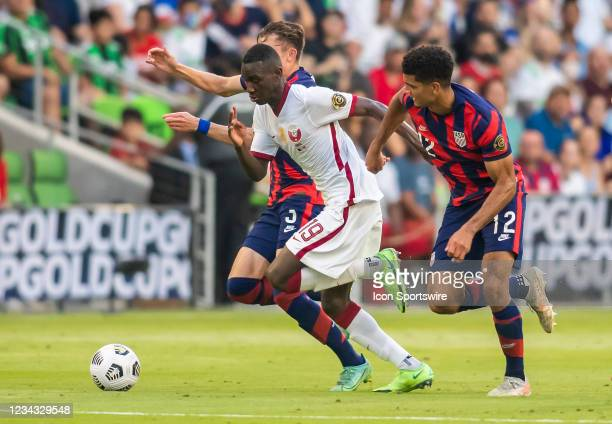 Qatar forward Al Moez Ali charges between US defenders during the Gold Cup semifinal match between the United States and Qatar on Thursday July 29th,...
