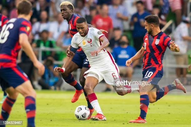 Qatar midfielder Abdulaziz Hatim attempts to maneuver past US defenders during the Gold Cup semifinal match between the United States and Qatar on...