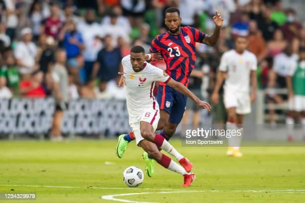 Qatar midfielder Abdulaziz Hatim maneuvers past a leaping Qatar midfielder Assim Madabo during the Gold Cup semifinal match between the United States...