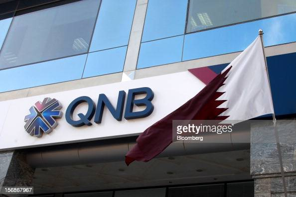 A Qatar national flag flies outside a branch of the Qatar