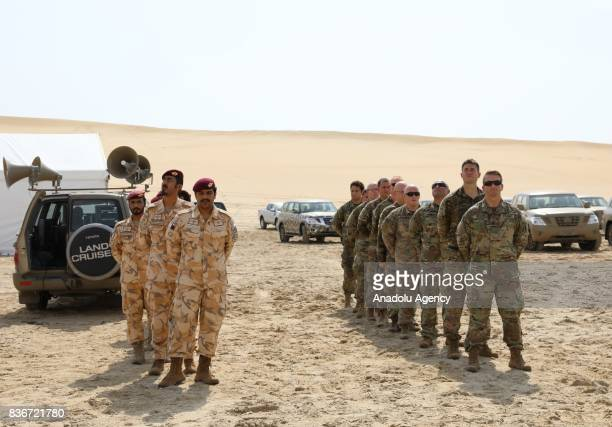 Qatari and US soldiers watch the parachute exercise during a joint military drill between Qatar and USA in Doha Qatar on August 22 2017