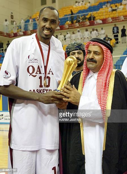 Qatari basketball national team's captain Yassin Ismail receives the trophy from Sheikh Saud bin Ali al-Thani, the vice president of Qatar's Olympic...