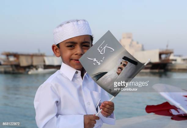 A Qatari boy holds a portrait of the Emir as Qataris gather in the streets of Doha to welcome back the Emir upon his returned from his first trip...