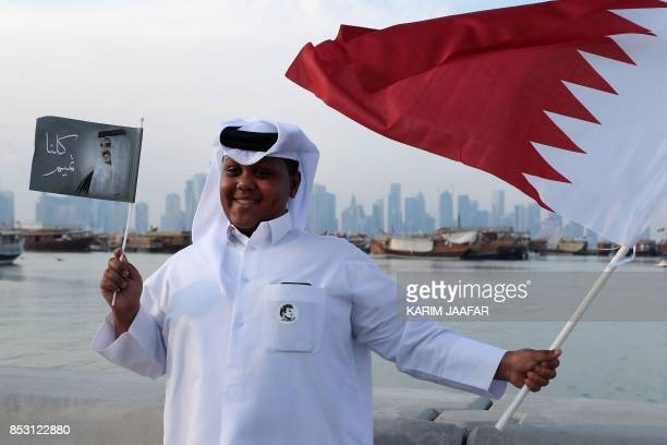 A Qatari boy waves his national flag portrait of the Qatari Emir as Qataris gather in the streets of Doha to welcome back the Emir upon his returned...