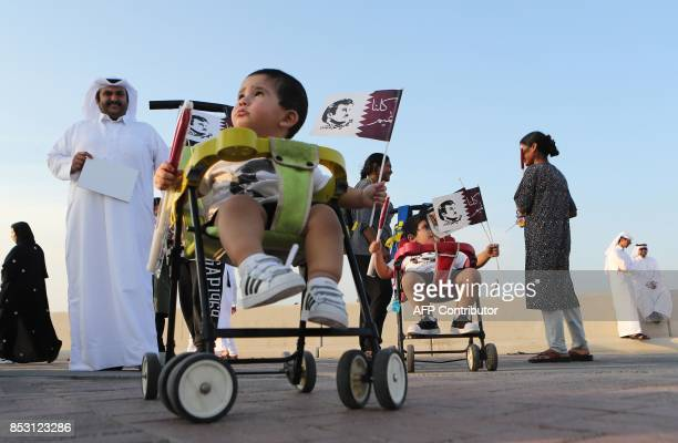 A Qatari child holds a flag bearing a portrait of the Emir as Qataris gather in the streets of Doha to welcome back the Emir upon his returned from...