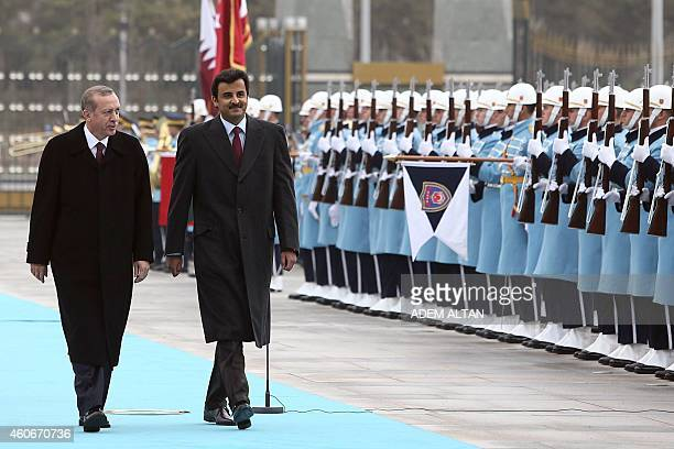 Qatari Crown Prince Sheikh Tamim bin Hamad bin Khalifa alThani and Turkish President Recep Tayyip Erdogan walk past a guard of honor during an...