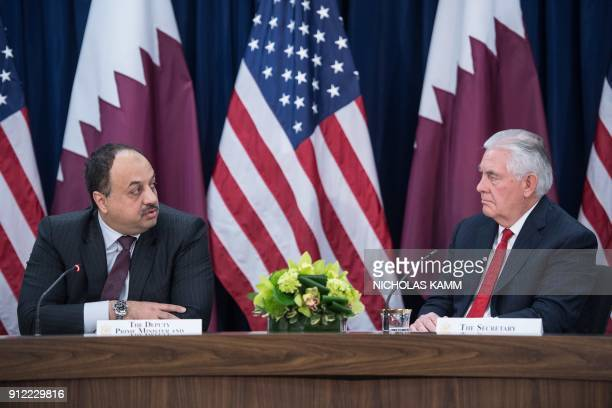 Qatari Defense Minister Khaled bin Mohammed alAttiyah looks at US Secretary of State Rex Tillerson as he speaks before the two countries signed...