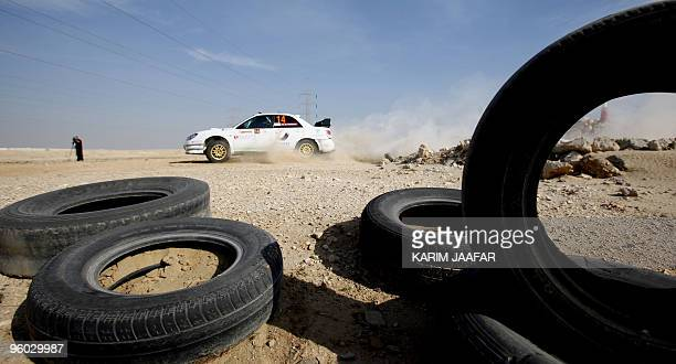 Qatari driver Sheikh Hamad alThani and codriver Aref Yousef Mohammad drive their Subaru 2008 during the Qatar International Rally competition in Doha...