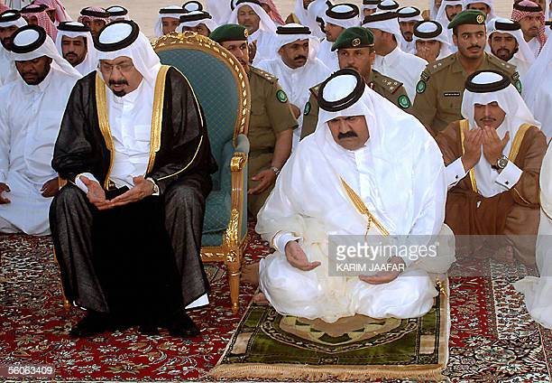 Qatari Emir Sheikh Hamad bin Khalifa alThani and his father Khalifa alThani perform performs the Eid alFitr prayer at a mosque in Doha 03 November...