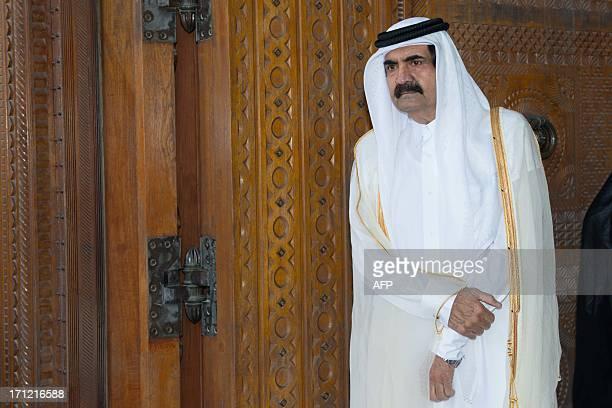 Qatari Emir Sheikh Hamad bin Khalifa al-Thani awaits for France's President Francois Hollande prior to a welcoming ceremony at the Diwan Emiri as...
